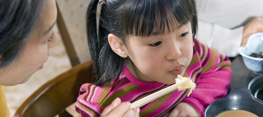mother feeding daughter with chopsticks