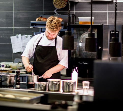 chef working alone in kitchen preparing delivery food